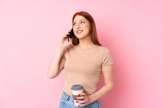 Caffè della tenuta della giovane donna di redhead da portare via e un cellulare