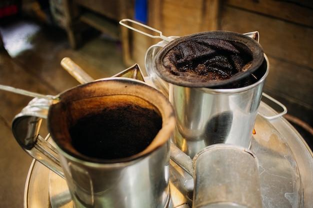 Caffè della via di stile tailandese con il vaso e la rete del filtro.