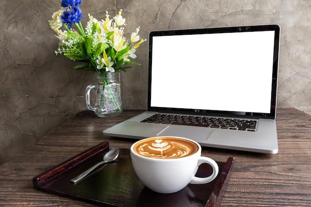 Caffè di arte del latte con lo schermo in bianco del computer portatile sulla tavola di legno