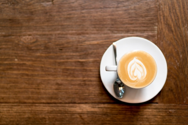 Caffè di arte del latte di vista superiore su di legno. schiuma di latte art a forma di cuore.