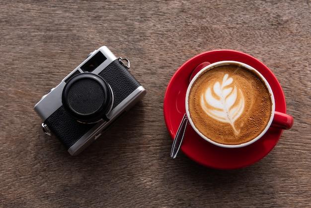 Caffè di arte del latte e macchina da presa sulla tavola di legno, vista superiore