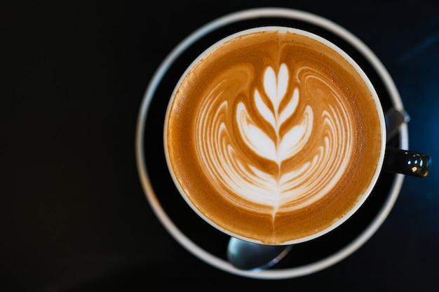 Caffè di arte del latte in tazza nera sulla tavola nera, tono scuro