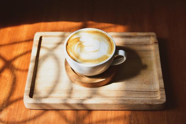 Caffè di arte del latte su luce solare di legno della tavola alla finestra