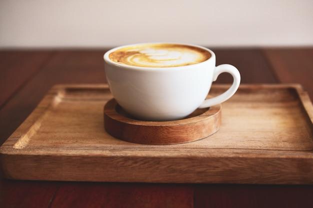 Caffè di arte del latte sulla tavola di legno su tempo del caffè