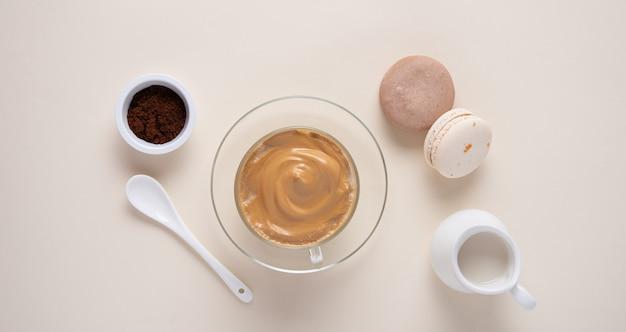 Caffè di dalgona in tazza con i maccheroni su fondo giallo
