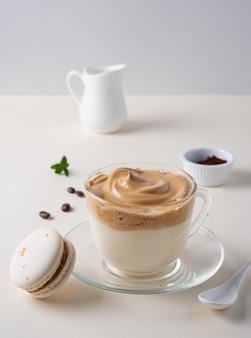 Caffè di dalgona in tazza con un maccherone su fondo giallo