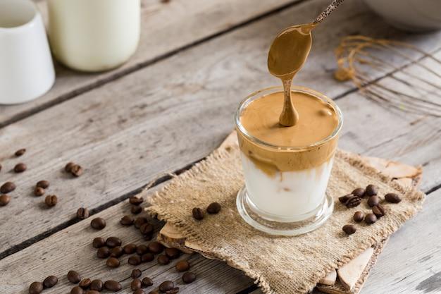Caffè di dalgona in un bicchiere su un tavolo di legno
