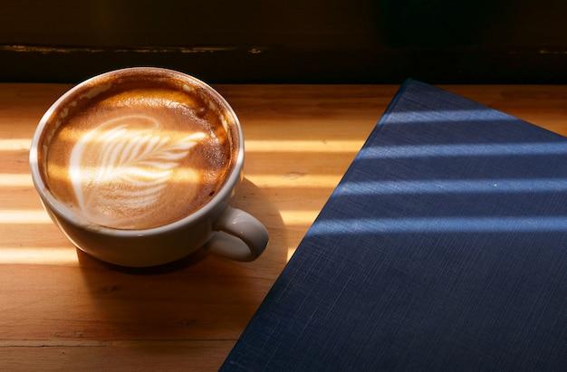 Caffè di lattee su fondo di legno e concetto del copyspace, della bevanda e della bevanda.