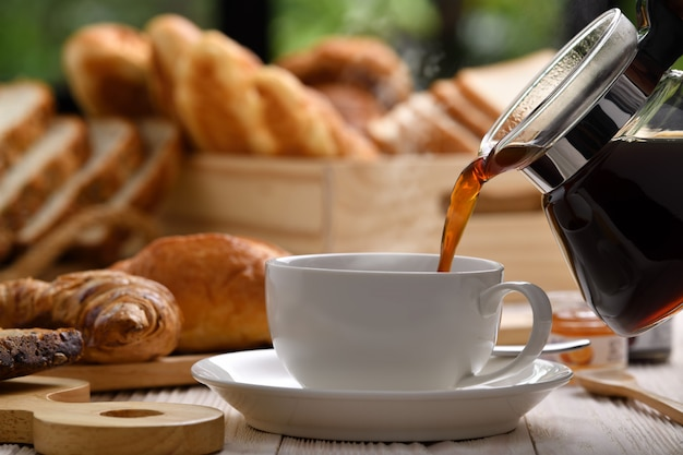 Caffè di versamento con fumo su una tazza con pane o panino, croissant e prodotti da forno sulla tavola di legno bianca