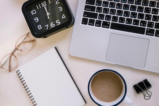 Caffè e articoli di cancelleria vicino a orologio e computer portatile