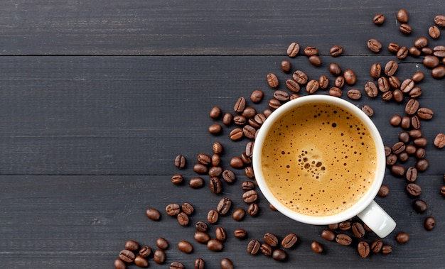 Caffè e fagiolo caldi su fondo di legno. vista dall'alto