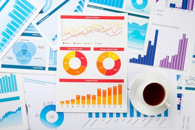 Caffè e grafici aziendali sul tavolo. il concetto di definizione delle informazioni chiave in un'azienda.