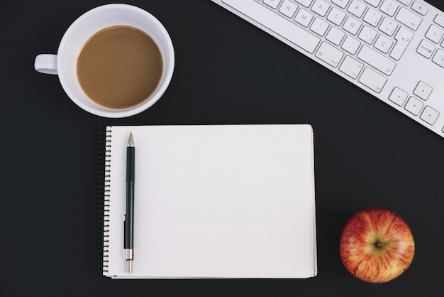 Caffè e mela vicino a notebook e tastiera