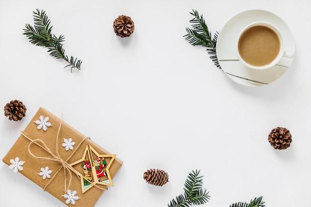 Caffè e presente vicino a rametti e coni