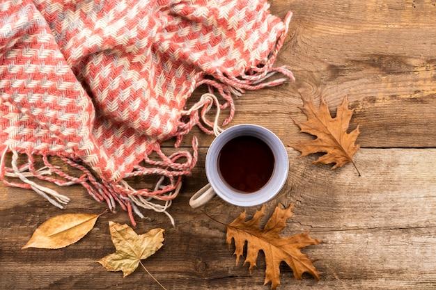 Caffè e sciarpa su fondo di legno