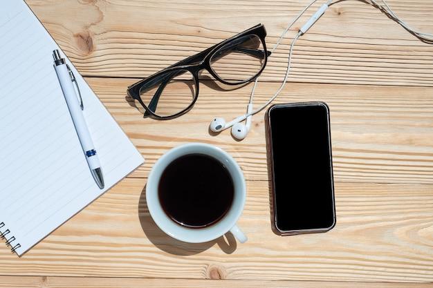 Caffè e smart phone con penna, notebook
