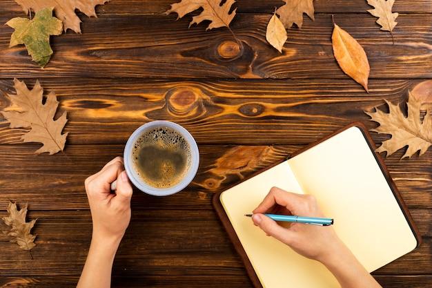 Caffè e taccuino su fondo di legno