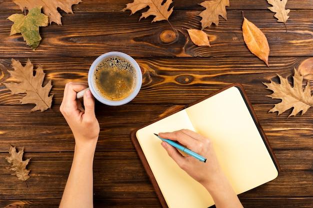 Caffè e taccuino sul fondo delle foglie di autunno
