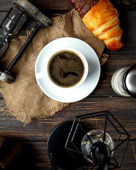 Caffè espresso caldo con cornetto sul tavolo