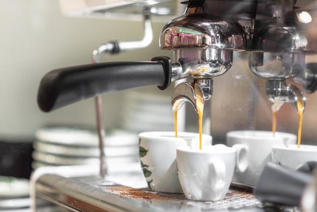 Caffè espresso che versa dalla macchina per caffè espresso