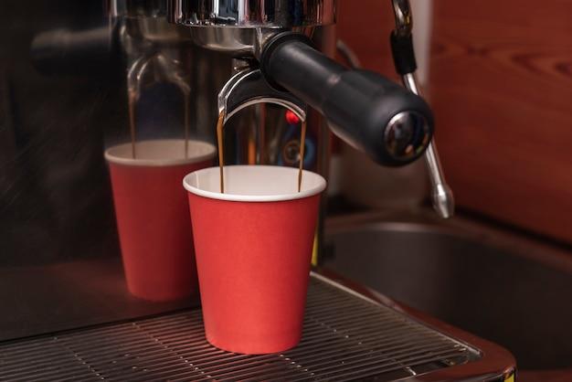 Caffè espresso del primo piano che versa nella tazza di caffè