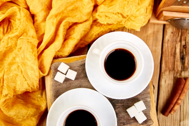 Caffè espresso di due tazze di caffè vicino al cubo dello zucchero