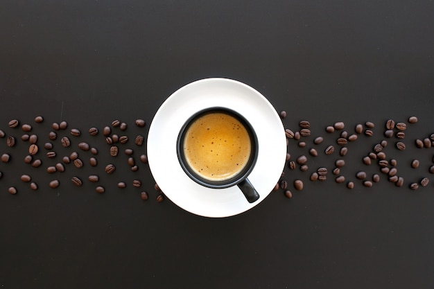 Caffè espresso e chicco di caffè caldi sulla tavola nera