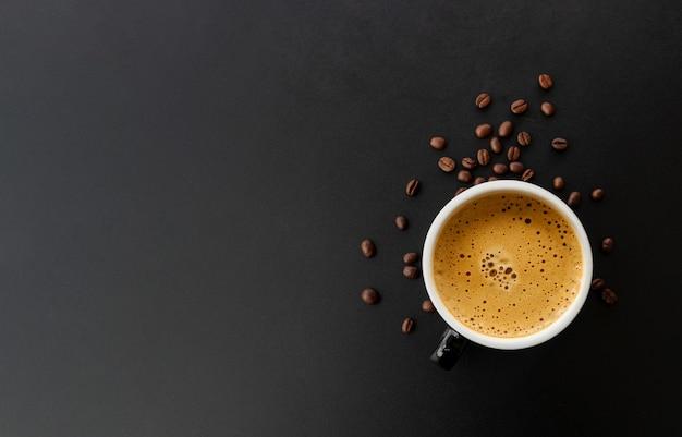 Caffè espresso e chicco di caffè caldo sulla tabella nera