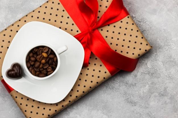 Caffè espresso in tazza bianca, regalo con burocrazia e cioccolatini. vista dall'alto, copia spazio. sfondo di cibo