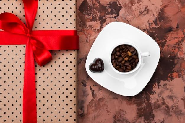 Caffè espresso in tazza bianca, regalo con la burocrazia e cioccolatini su uno sfondo scuro. vista dall'alto. sfondo di cibo