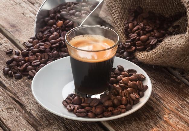 Caffè espresso in tazza di vetro con chicchi di caffè.
