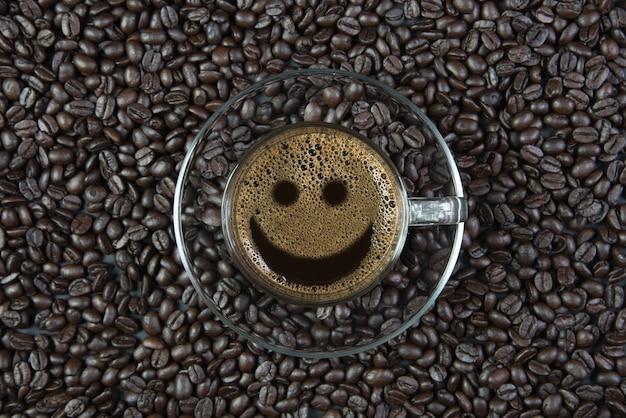 Caffè espresso in un bicchiere sul tavolo di legno / sorriso caffè