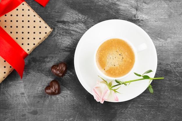 Caffè espresso in una tazza bianca, una rosa rosa, un regalo con una burocrazia e cioccolatini su uno sfondo scuro. vista dall'alto. sfondo di cibo