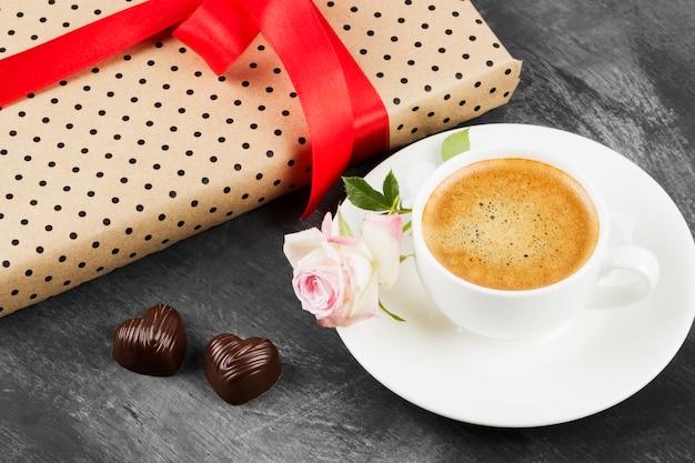 Caffè espresso in una tazza bianca, una rosa rosa, un regalo con una burocrazia e cioccolatini su uno sfondo scuro