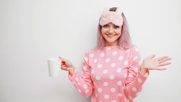 Caffè felice di mattina della bevanda della giovane donna. bella ragazza in pigiama rosa e maschera da notte