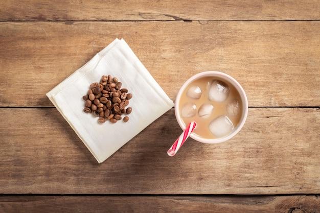 Caffè freddo rinfrescante e tonificante in un bicchiere e chicchi di caffè su un fondo di legno. caffetteria concept, dissetante, estate. vista piana, vista dall'alto