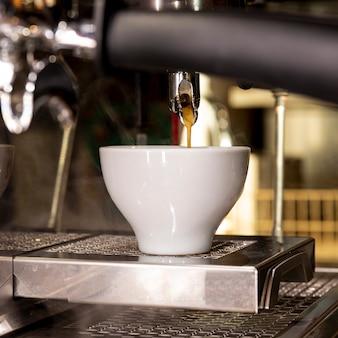 Caffè fresco del primo piano che versa nella tazza