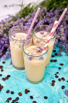 Caffè ghiacciato con lavanda in vetro e chicchi di caffè su sfondo blu