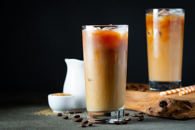 Caffè ghiacciato in un bicchiere alto con crema versata sopra.