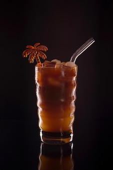 Caffè ghiacciato in un bicchiere su sfondo nero. bevanda o cocktail fredda del caffè con ghiaccio su un fondo scuro