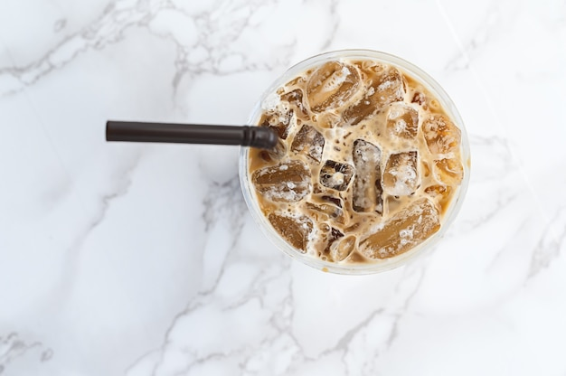 Caffè ghiacciato nella fine di plastica di vista superiore della tazza su
