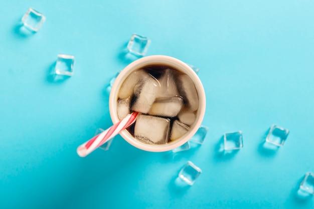 Caffè ghiacciato rinfrescante in un bicchiere e cubetti di ghiaccio su una superficie blu. concetto estate, cola con ghiaccio, cocktail rinfrescante, sete. vista piana, vista dall'alto
