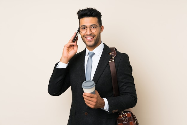 Caffè giovane bello della tenuta dell'uomo dell'uomo d'affari da portare via sopra fondo isolato