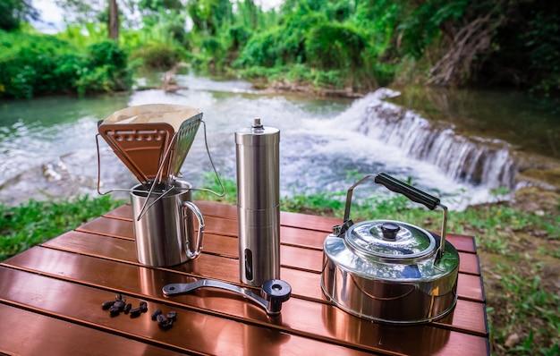Caffè gocciolante mentre si accampa vicino alla cascata
