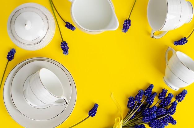 Caffè in porcellana bianca o set da tè con fiori di muscari su giallo