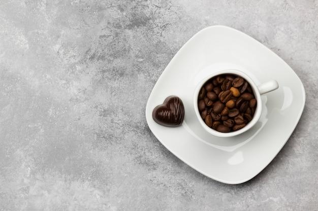 Caffè in tazza bianca e cioccolatini. vista dall'alto, copia spazio. sfondo di cibo