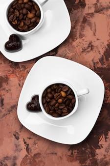Caffè in tazza bianca e cioccolatini. vista dall'alto. sfondo di cibo
