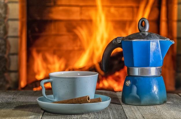 Caffè in tazza e caffettiera geyser prima accogliente caminetto, in casa di campagna, vacanze invernali.