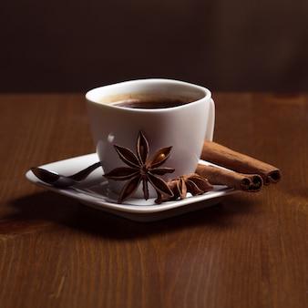 Caffè in una tazza bianca con cannella su una tavola di legno