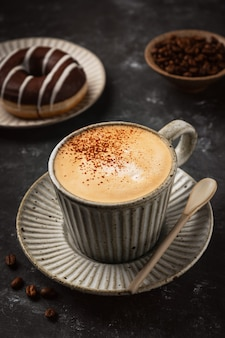 Caffè in una tazza con una ciambella e chicchi di caffè